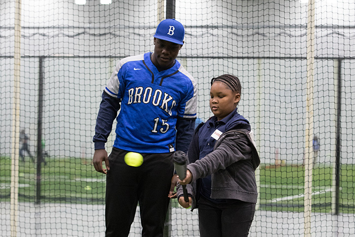 Baseball coach helps child learn to bunt.