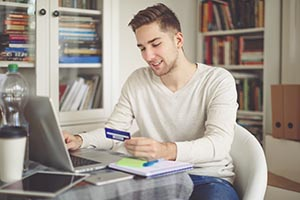 young man holding credit card and working on laptop
