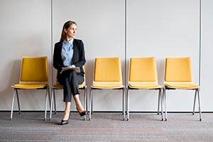 Young woman waiting in a row of empty chairs