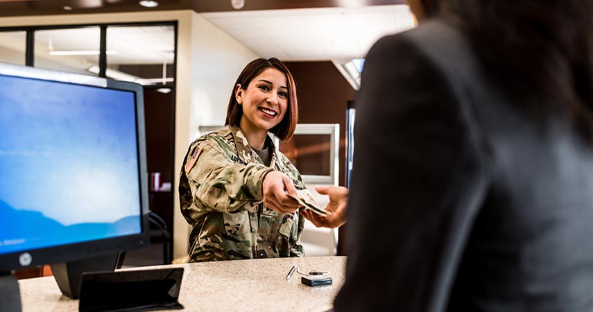 Woman in camo passing a credit card to someone behind the counter