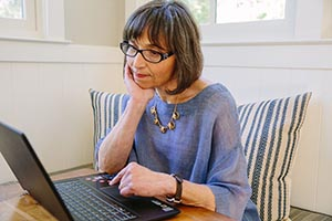 Older woman looking thoughtfully at her laptop screen