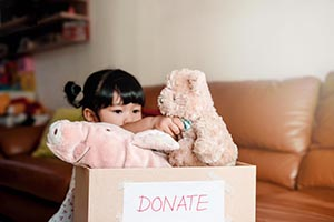 Little Asian girl putting stuffed animals into donation box