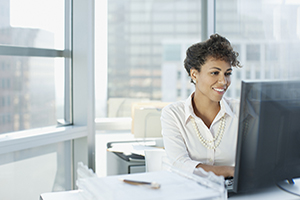 Business woman smiling while at laptop
