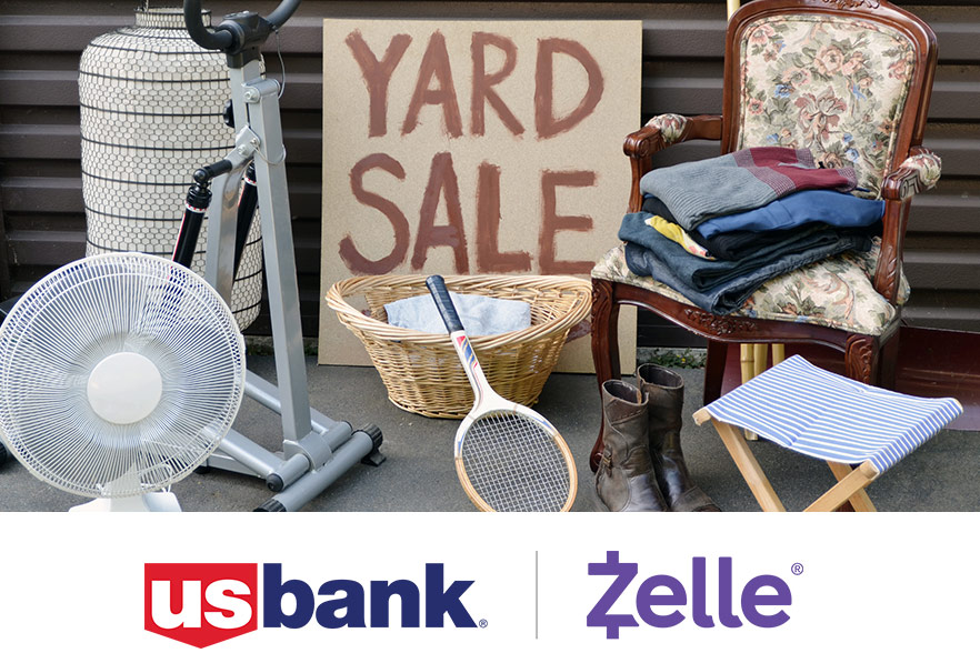 Yard sale: gray corrugated metal background with sign, white fan, tennis racket, wicker basket, accent chair and clothes in foreground, red and blue us bank logo and purple zelle logo